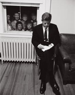 Seated Kennedy looking at notes while a crowd peers in through a window behind him