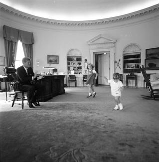 Two small children running across the office while a seated JFK observes them