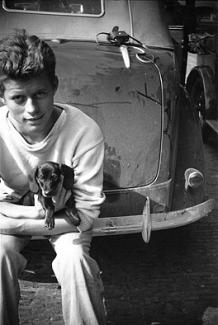 A young Jack Kennedy sitting on the bumper of a car, holding a puppy