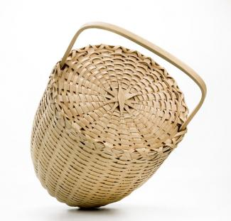 A basket with an oval shape and a lid and handle.