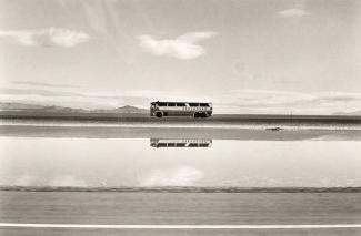 A photograph of a bus in a Utah landscape by automobile.