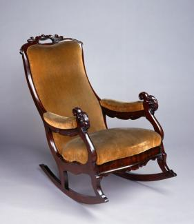 A mahogany rocking chair with yellow upholstery.