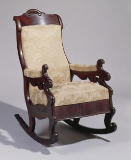 A mahogany rocking chair with creme upholstery.