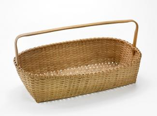A basket that is long and narrow with a handle.