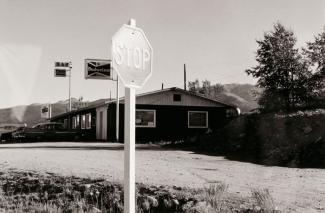 A photograph of a Colorado landscape with stop sign and building taken by automobile.