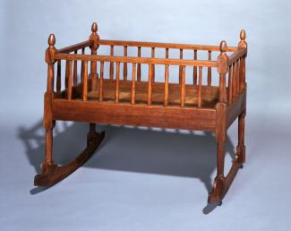 A walnut Windsor style cradle.