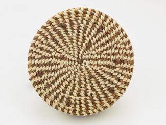A basket that's circular with a pattern woven into it.
