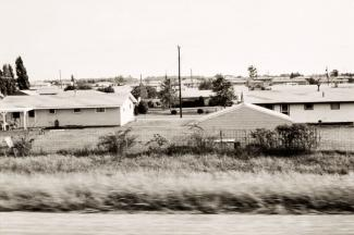 A photograph of a Illinois landscape with houses taken by automobile.