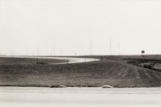 A photograph of an Ohio landscape with a road taken by automobile.