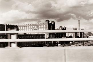 A photograph of a Connecticut landscape with a building taken by automobile.