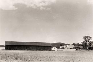 A photograph of a Massachusetts landscape with a building taken by automobile.