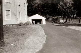 A photograph of a Massachusetts landscape with a house and driveway taken by automobile.