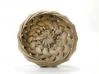 A basket that is small and round with a spiral pattern weave.