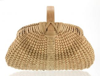 A basket that has a bigger base and compresses as it gets closer to the handle.