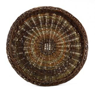A basket that is the shape of a large plate with a multicolored design.