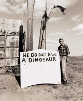 "A photograph of a sign with a man saying ""we do not have a dinosaur""."
