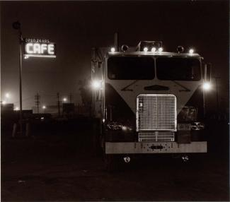A photograph of a truck stop with a semi and cafe night taken at night.