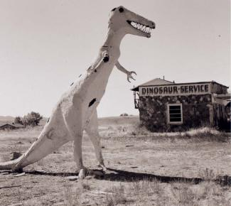 A photograph of a gas station with a dinosaur sculpture.