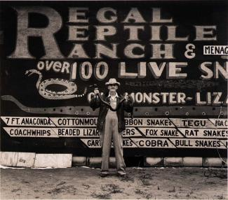A photograph of a man holding a snake in front of a sign.