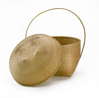 A basket that has a square base that flares our with a circular top and a long thin circular handle.