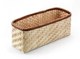 A basket that is long and rectangular with a dark trim and a light body.