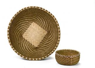 A large basket shaped like a large bowl and a small circular basket made with a spiral weave. The larger basket has a light square patch in its center.