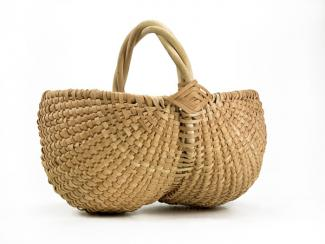 A basket with two circular sides that come together in the middle and are connected to a handle.