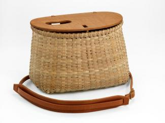 A small basket with a rectangular base and a circular top that has a leather strap handle.