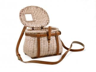 A basket with a rectangular base that has a circular top with a lid and leather accents, and a leather strap.