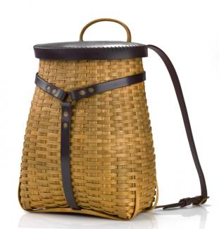 A tall basket with a rectangular bottom and a circular top with backpack straps made of leather.