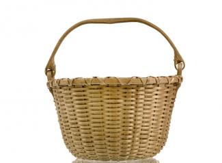 A small basket that's circular with a handle that goes across the body of the basket.