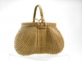 A basket that is circular, but the extension of the handle compresses the shape in the middle.