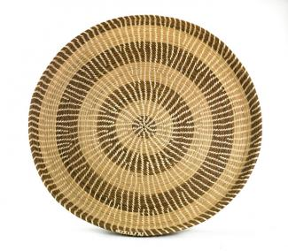 A basket that's circular and flat like a plate with two different colors.