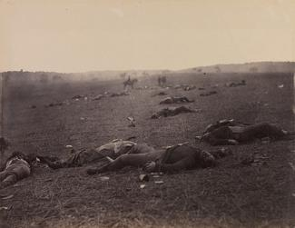 O'Sullivan's albumen print of a battlefield with dead soldiers scattered throughout.
