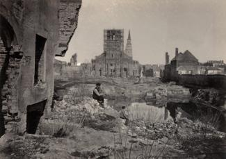 Barnard's vintage albumen print of a town with a man sitting on rocks in the middle ground and the surrounding town in the background.