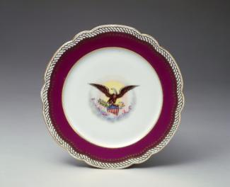 An image of a porcelain dinner plate with a maroon outer circle and white middle with eagle.