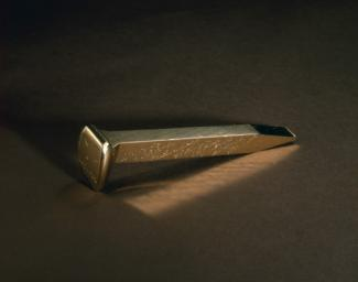 An image of a gold and copper railroad spike.