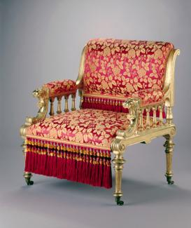 An image of a gilded ash armchair with gold accents and red upholstery.