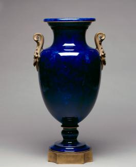 An image of a porcelain and gilded metal vase that's dark blue with brass handles.