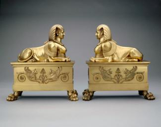 An image of two brass andirons with sphinx tops.