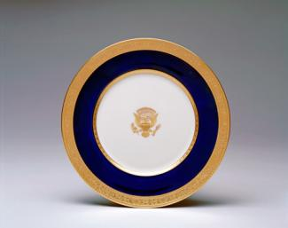 An image of a porcelain service plate with gold rim, blue outer circle and crest in the middle.