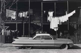 A gelatin silver print of a street with a car in the foreground, clothes handing in the middle ground and a building in the background.