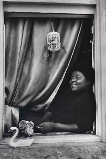 A gelatin silver print of a woman leaning in her window looking out with a curtain behind her.