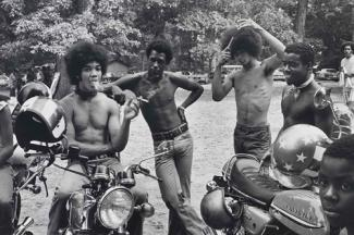 A gelatin silver print of four main male figures around motorcycles with trees in the background.