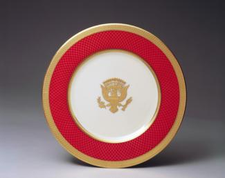 An image of a porcelain service plate with gold rim, red outer circle and crest.