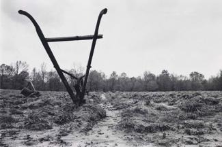 An gelatin silver print of a muddy field with a farming tool.