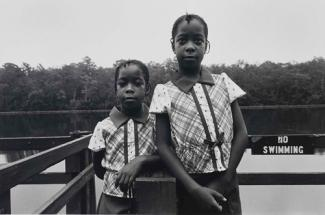 A gelatin silver print of two young girls standing in front of a body of water.