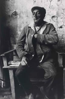 A gelatin silver print of a man sitting and smoking with one hand in his jacket.