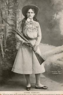 Fox's photomechanical print of Annie Oakley in a dress, hat, and carrying a shotgun.