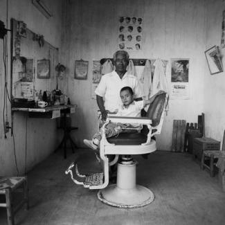 Gleaton's gelatin silver print of a little boy in a salon chair posing with his barber.